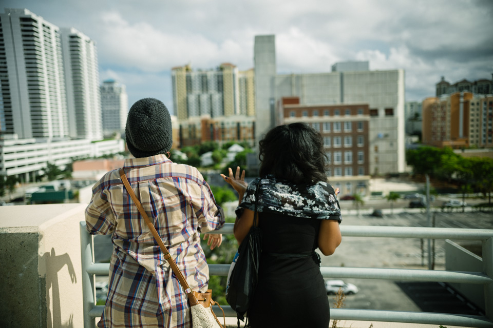 Josephine and Sol are standing on top of a parking garage roof, in conversation.